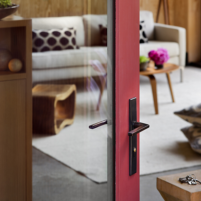 A close up view of the Baldwin Lakeshore entryset in Oil Rubbed Bronze, mounted on a red glass door.