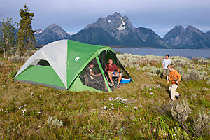 The image depicts a family of four (husband, wife, two young boys) camped in a grassy field with a lake and mountains in the background. The mother and father are relaxing in a Coleman  green and white dome tent while the boys run around in front.