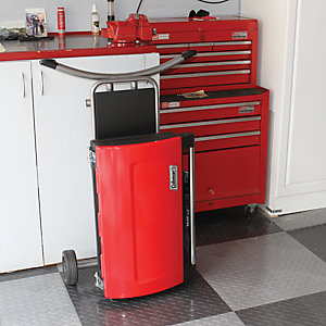 A foleded up NXT grill standing upright in a garage for storage. The grill is in front of a cabinet and a wheeled tool chest.