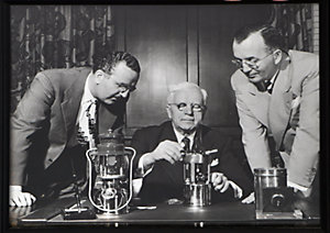 A black and white photo of W.C. Coleman sitting at a desk assembling a lantern with two other men, one on either side, leaning over and watching him work.