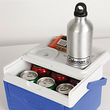 A small Coleman beverage cooler with the lid slid open to reveal several cans on the inside and a Coleman-branded stainless steel water bottle resting in the cup holder on the lid. A small bag of peanuts is also sitting on the lid behind the water bottle.