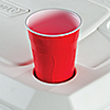 Closeup of a red Solo cup resting in the cupholder on top of a Coleman cooler