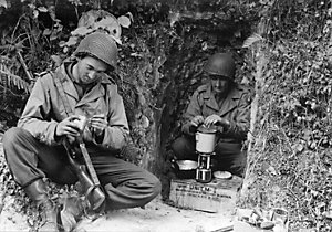 A black and white photo of two soldiers sitting in front of a hillside. One soldier is in a hollowed-out space; the other is in front and to the left. The solders are eating canned rations, and a Coleman pocket stove is sitting on a box in front of the solider in the hollow.