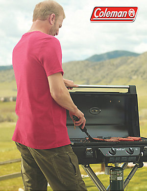 A  man is flipping a burger on a Coleman camping grill; an assortment of hotdogs and hamburgers are on the grill. His right side faces the camera with his right hand holding the spatula and his left hand resting on open grill lid handle. The foothills to the Rocky Mountains are visible in the background. The Coleman logo is on the top right-hand corner.
