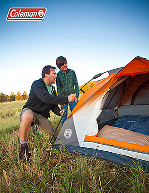A father and son are setting up a Coleman dome tent in a grassy field. The father is kneeling to the left side of the tent adjusting one of the poles while the son watches over his left shoulder. The image also displays the Coleman logo in the top left corner.