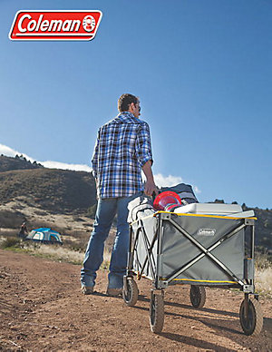 A man, with his back to the camera, pulls a Coleman camp wagon (loaded with various outdoor equipment) up a dirt trail on one of the Rocky Mountain foothills. A larger hill and tent are visible in the background. The Coleman logo is also placed in the top left-hand corner of the image.