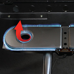 A closeup of an NXT burner with Heat Core technology. The burner is shaped like a racetrack with the flames on the outer edges. Towards the left end, there is a separate circular cutout with more flames around the circle as well as an arrow graphic that is turning up and out of the center of the core, demonstrating the heat flow pattern.