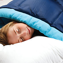 A woman sleeping in a Coleman sleeping bag with her head resting on a pillow. The ComfortCuff rests gently on her cheek.