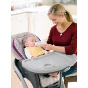 child being bottle fed inside blossom high chair image number 1