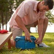 man placing granola bar into side storage of sport flex 30 can soft cooler image number 6