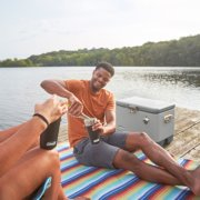 friends by lake sharing drinks from steel belted coolers in tumblers image number 6