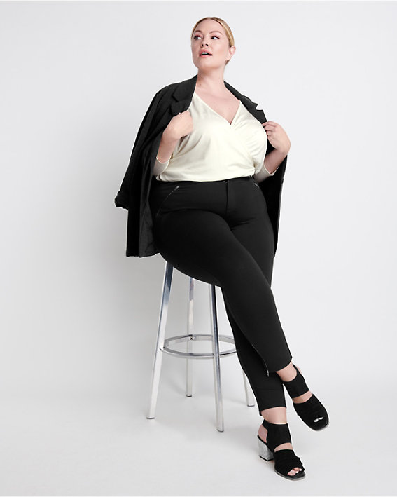 A brunette woman wearing a plus size crossover knit top with black jeans