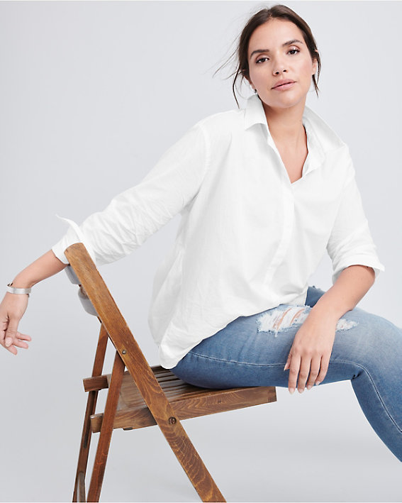 A brunette woman wearing a well fitted plus size classic long sleeve organic cotton white shirt and jeans.