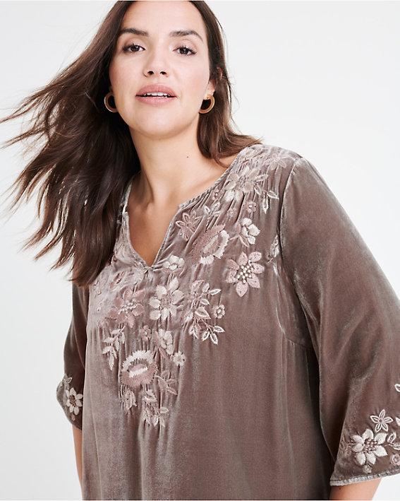 A brunette woman wearing a plus size floral velvet top