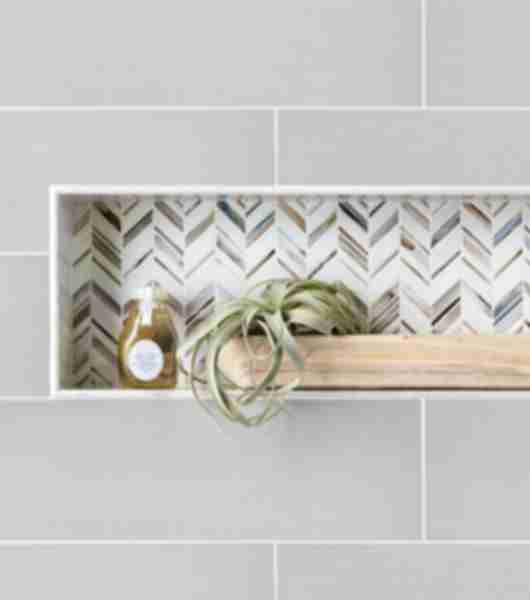 Recessed shelf with blue, brown, and white chevron mosaic. A plant and body wash sit on the shelf.