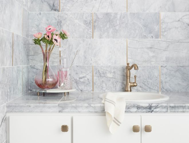 White grey carrara marble bathroom vanity wall gold accents.
