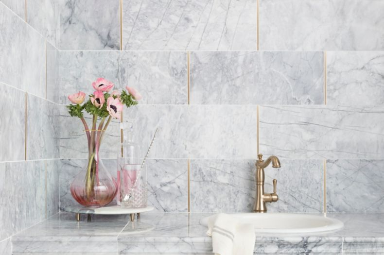 Sophisticated white and grey carrara marble wall with gold accents on kitchen backsplash.