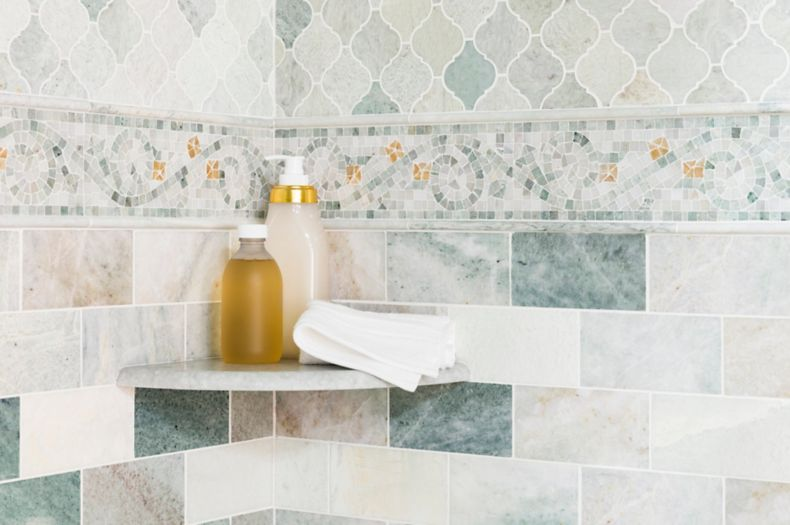 Corner of shower with green marble subway tile and mosaics on walls.