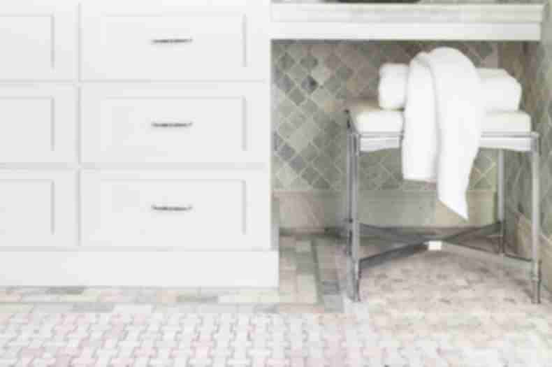 Traditional bathroom with green marble arabesque wall tile and basketweave floor tile.