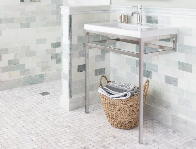 Bathroom with green marble on wall with white basketweave marble tile on floor.