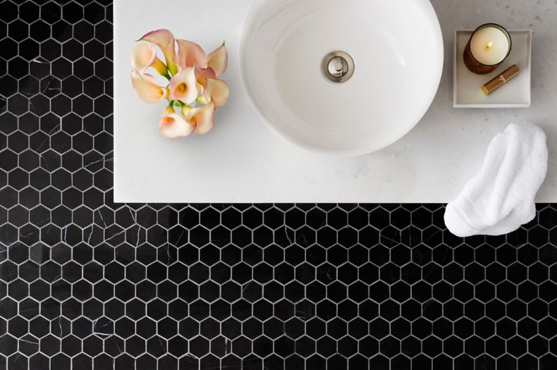 Sophisticated bathroom with black marble hexagon mosaic on floor.