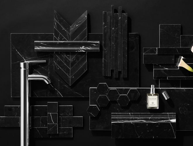 Black Marquina marble tile in various shapes and sizes with chrome faucet,  calla lily, and perfume bottle.