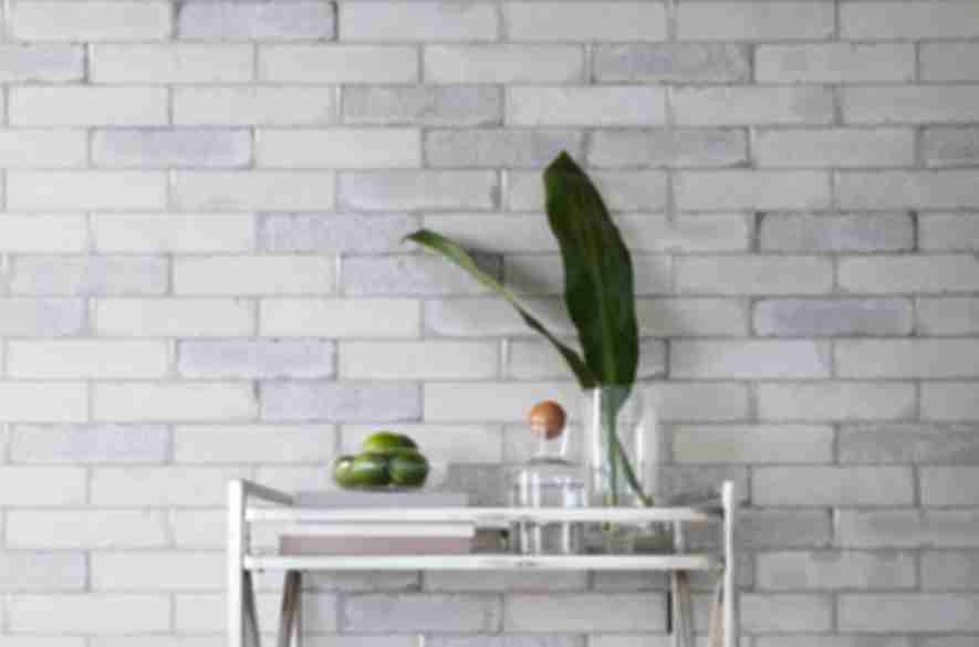 Industrial bar area with grey brick wall and silver accents.