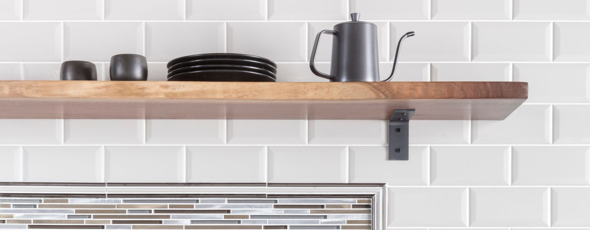 Coffee bar in kitchen with white bevel-edge subway tile and metallic stria accent tile as backsplash.
