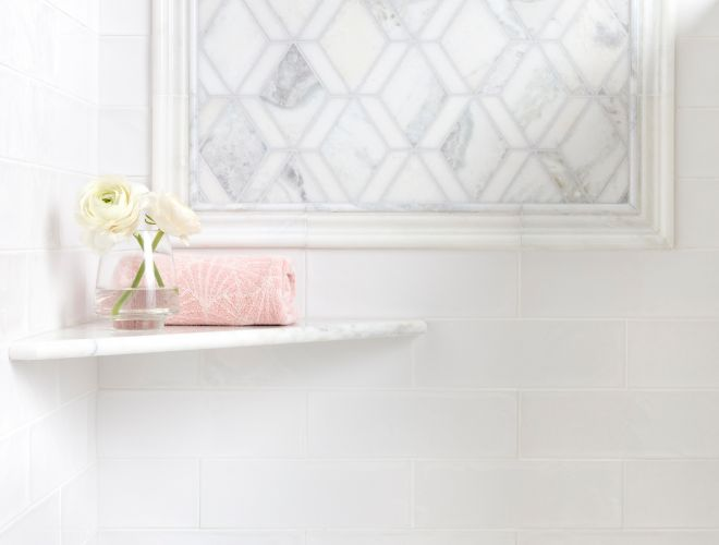 Feminine shower with white marble mosaic and white subway tile.