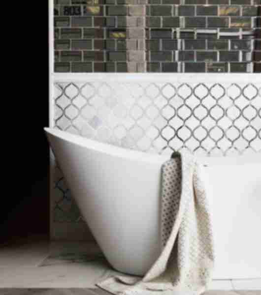 White arabesque and mirror subway tile in bathroom with elegant freestanding tub.