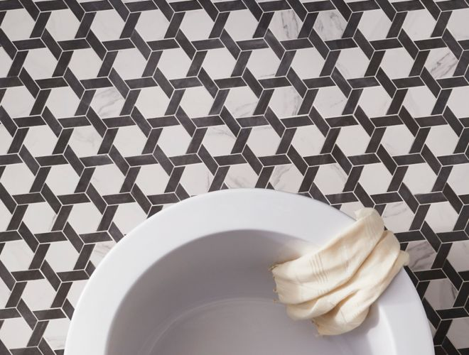Black and white hexagon-shaped, marble-look floor tile in bathroom with freestanding tub.