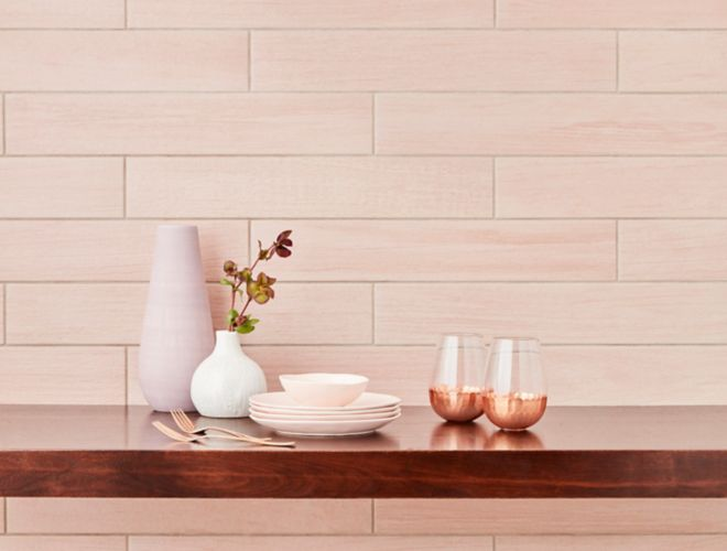 Blush pink wood-look wall tile in kitchen with feminine dishware.