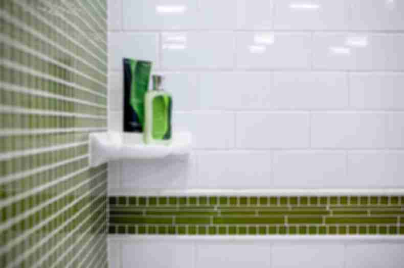 White subway wall tile and green glass mosaic tile on shower wall.