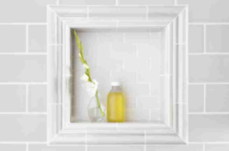 Subway tile on shower wall with recessed shelf framed by ceramic trim pieces.