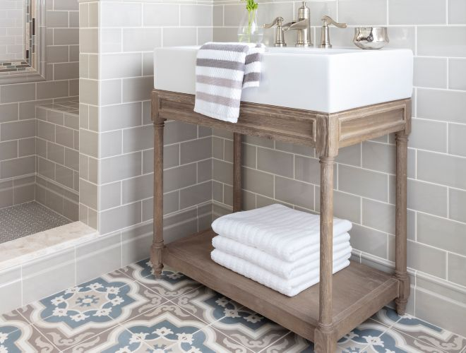 Modern farmhouse bathroom with subway wall tile and brown and blue encaustic floor tile.