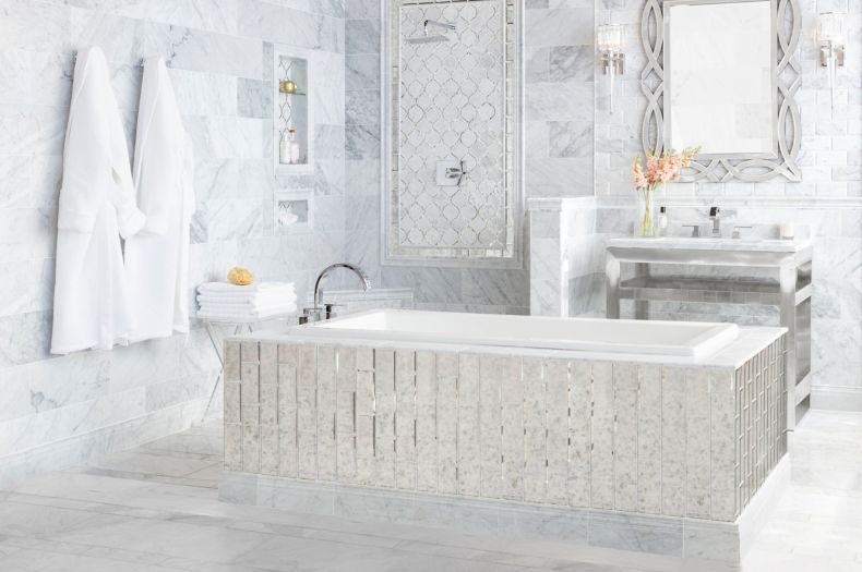 Elegant bathroom with white marble tile and antique mirror accents.