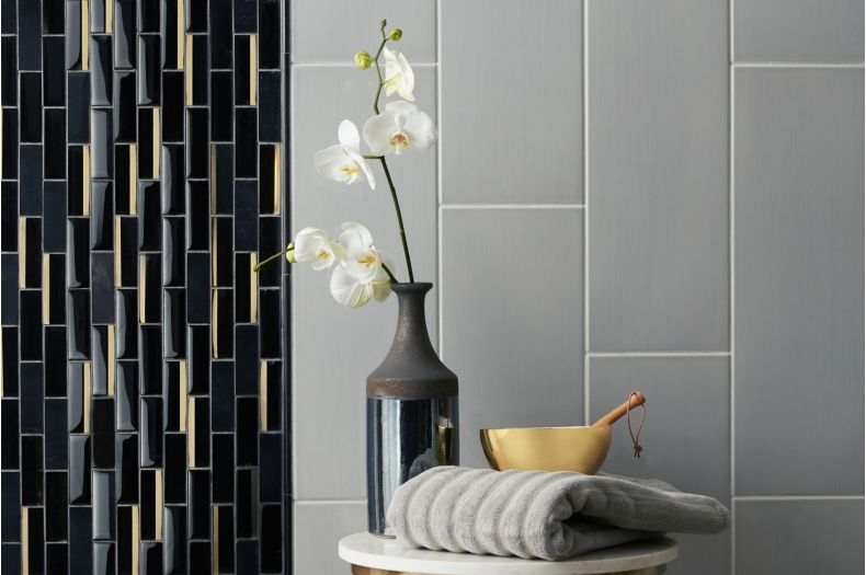 Contemporary shower wall with grey large-format tile and black and gold glass mosaic.