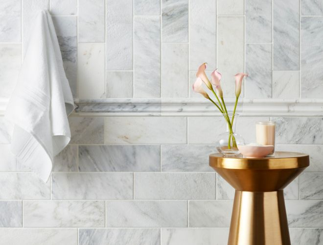 White and grey marble tiled shower wall with gold accent table.