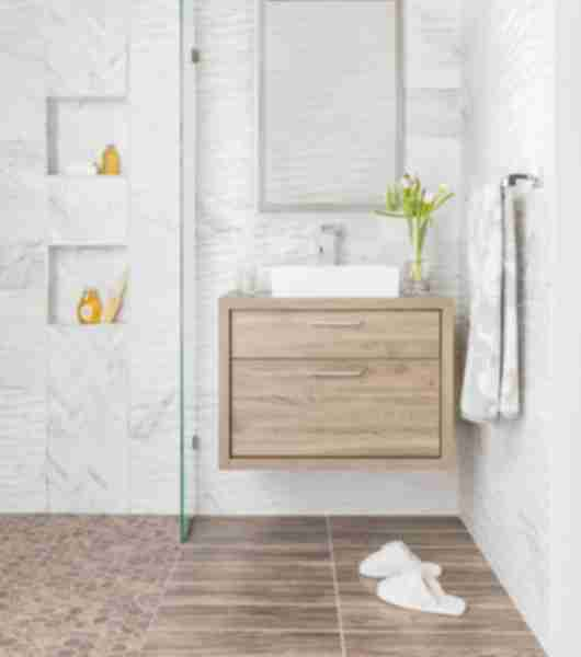 Bathroom with white carrara marble walls and warm wood accents.