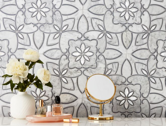 White marble mosaic with grey flower pattern on wall of elegant powder room.