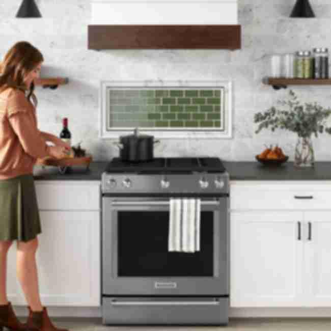 Marble kitchen with green glass backsplash.