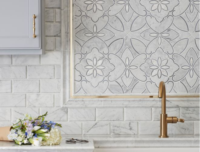 Kitchen backsplash with white marble mosaic in floral pattern and gold accents.