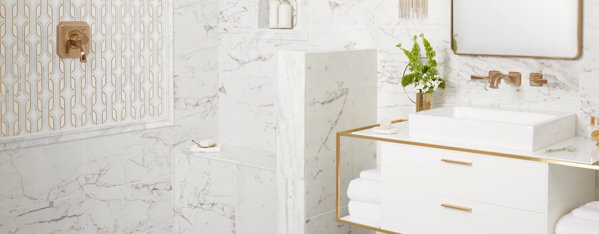 Glamorous bathroom with white marble and gold accents.