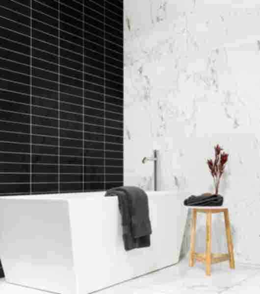 Black subway tile with white marble bathroom