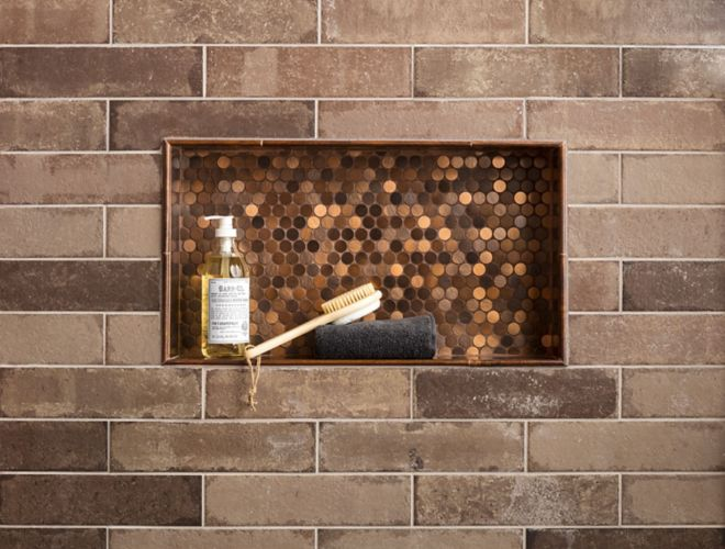 Brick subway wall tile in shower with copper penny round in recessed shelf.
