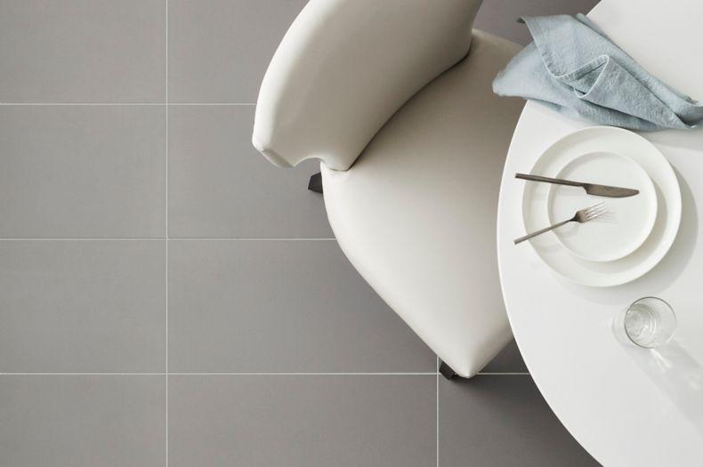 Sleek dining room floor with matte grey tile.