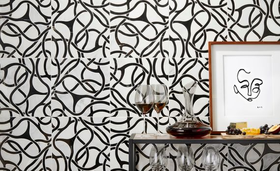 White and black marble mosaics with organic, vine-like pattern on wall of a bar area.