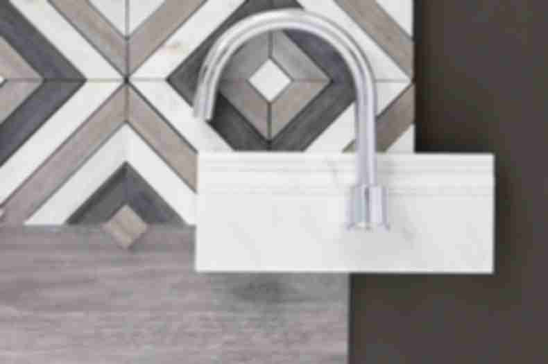 Mixed material brown and grey tiles, white marble skirting, and chrome faucet on dark grey table.