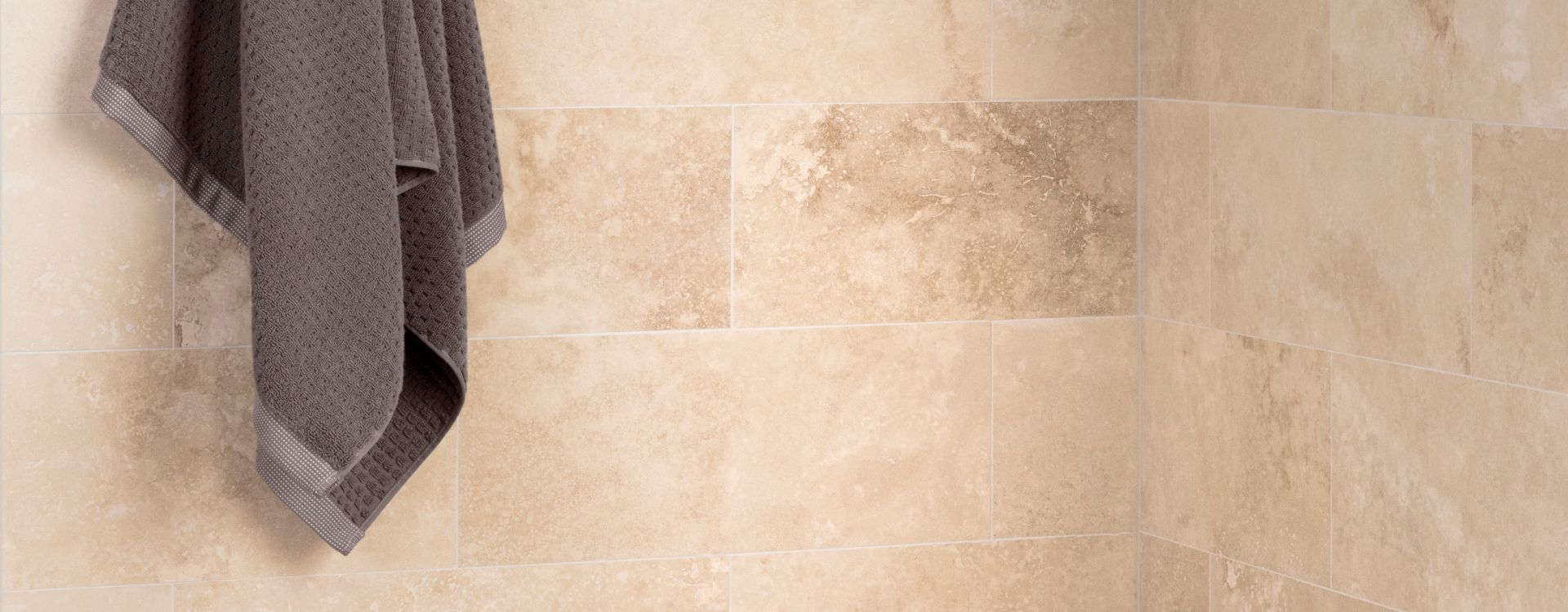 Corner of shower with shelf, brown stone wall tile, and brown and ivory glass mosaic.