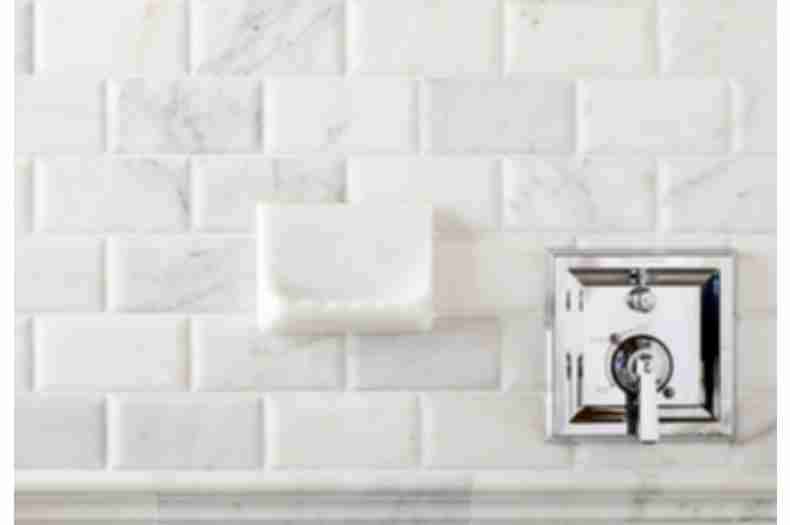 Shower wall with white marble subway tile and soap dish.
